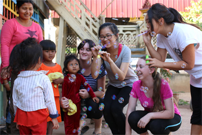 Teenagers volunteering in Cambodia on a Care & Community project enjoy some time with the children from their placement
