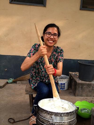 Projects Abroad female volunteer prepares local cuisine at her host family in Ghana, Africa