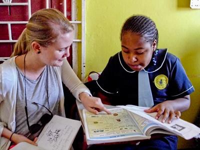 A Projects Abroad Jamaica volunteer helps somebody in a teaching project in Jamaica