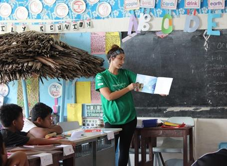 Volunteer reads a book to children at a Care placement in Samoa