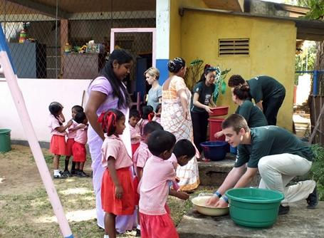 A volunteer in Sri Lanka demonstrates how to wash hands to a group of children.