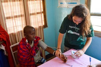 A female Projects Abroad volunteer in Tanzania measuring the blood pressure of a local woman