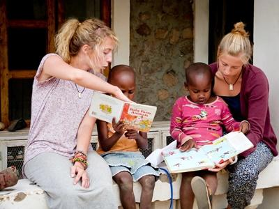 Projects Abroad volunteers in Tanzania reading books to children