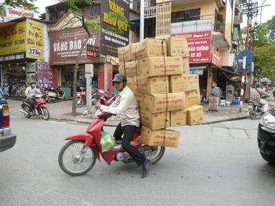 Volunteers in Vietnam get to experience the rich local culture - here, a man carries boxes on the back of his motorbike