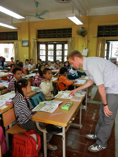 A Projects Abroad Teaching volunteer in Vietnam chats to children in a classroom