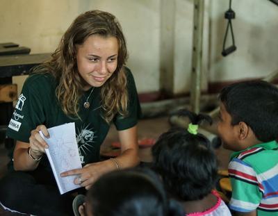 Children learn English with an Alternative Schoolies volunteer