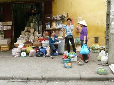 Vietnamese locals stand on street outside shop