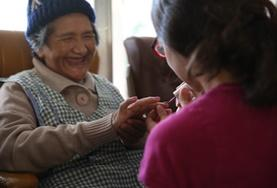 A Care volunteer gives a manicure to a woman during an outreach at an elderly home in Bolivia.
