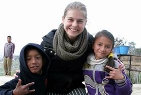 A childcare volunteer works closely with two children at a care centre in Nepal.