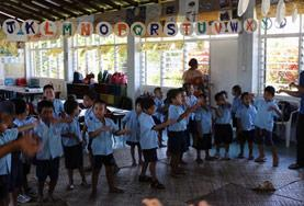 A childcare volunteer works with school children in a classroom in Samoa.