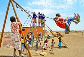 School children swinging together on a playground at our volunteer childcare placement in Tanzania.