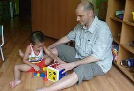 A Care volunteer works with a child in Vietnam, playing an educational game.