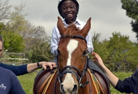 A volunteer supports a disabled boy as he rides his therapy horse at our Equine Therapy placement in South Africa.