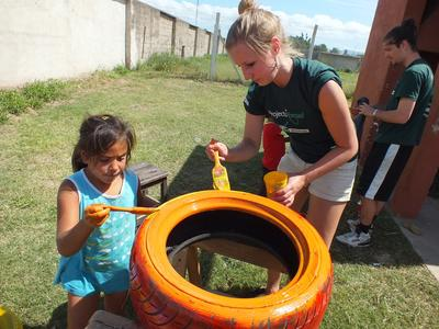 Projects Abroad Care volunteer in Argentina painting a tyre with a young girl