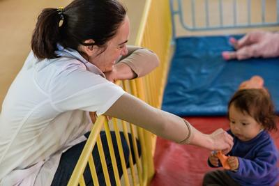 A Projects Abroad volunteer plays games with a child at a nutrition center in Cochabamba