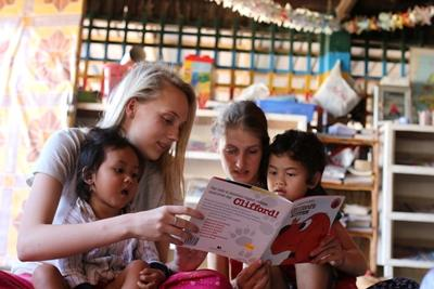 Young students who chose to volunteer abroad with Projects Abroad in Cambodia read with the children at a day care centre
