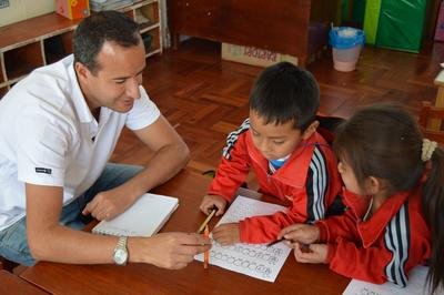 Male Projects Abroad volunteer assists children at a Care placement in Peru