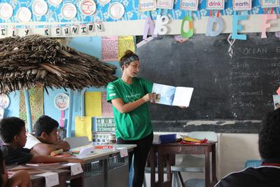 Projects Abroad volunteer reads a book to children at a Care placement in Samoa