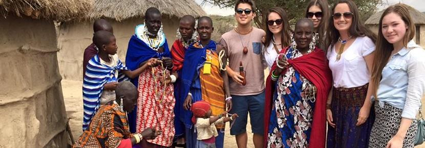 Projects Abroad Care and Community volunteers stand with local Tanzanians at a Masai village