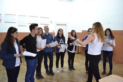 A group of teenagers listen to an Australian volunteer drama teacher in Romania, Eastern Europe.