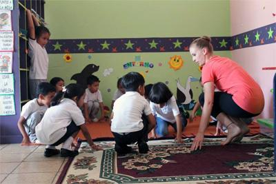 Projects Abroad volunteer teaches a group of children a dance at the Creative Arts Project in Ecuador