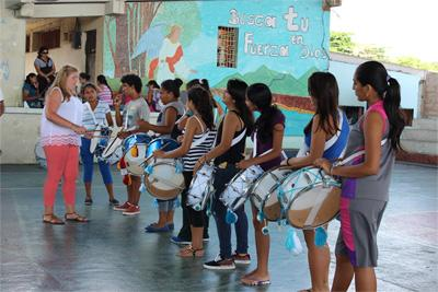 Projects Abroad volunteer teaches a group of children drums at the Music Project in Ecuador