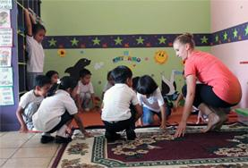 A Creative Arts volunteer working in Ecuador teaches a music lesson to local students.