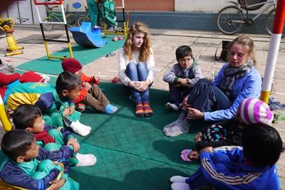 Two Projects Abroad volunteers sit in a circle with children at a care center in Nepal on the Care project