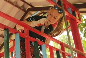 A Care & Community volunteer adds a coat of paint to playground equipment at a local care centre in Cambodia.