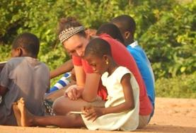 An adult volunteer works on a child's reading skills at a care centre during our Care & Community project in Ghana.