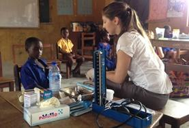A volunteer in Ghana takes basic measurements to check the general health of a child during a Public Health screening outreach.
