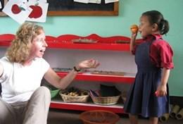 An older volunteer teaches a local school child in Nepal about English words through a practical exercise.