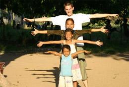 A High School Project volunteer poses in a creative way with the children from his Care & Community placement in Cambodia.