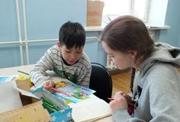 A High School Project volunteer works closely with a local child in Mongolia to improve his reading and literacy skills.