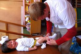 A high school student volunteering at our Medicine placement in Peru assists with dressing a baby.