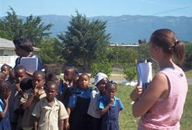 A Disaster Management volunteer talks to local children about an evacuation plan at a school in Jamaica.