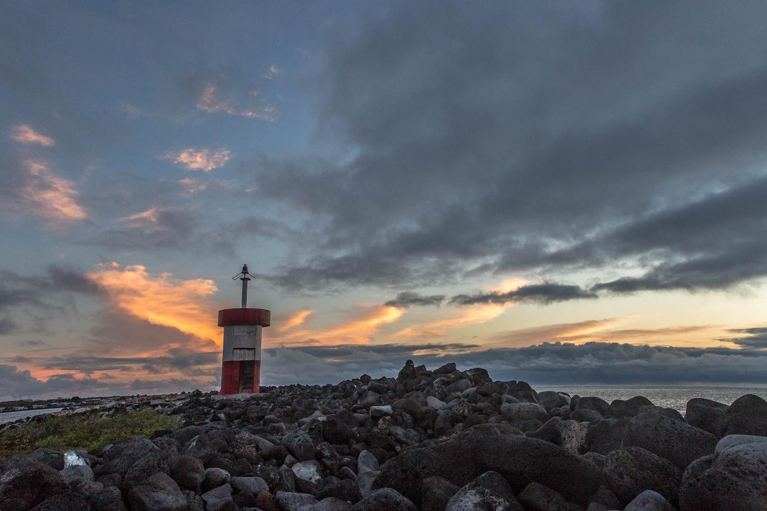Sunset behind the lighthouse of Punto Carola on San Cristobal Island