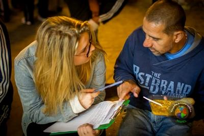 Projects Abroad Human Rights volunteer interviews a homeless man in order to try and help him get a pension and ID card