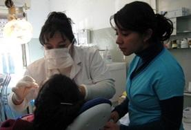 A volunteer observes as a local dentist examines a patient at our Dentistry internship placement in Argentina.