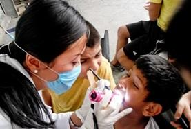 A Dentistry intern observes as a dentist performs a check-up on a boy in Guadalajara, Mexico.