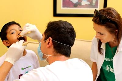 A child receives a dental check-up from a Dentistry volunteer in Mexico.
