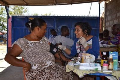 Projects Abroad volunteer takes the blood pressure of a patient in at a medicine placement in Ghana