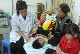 Medical interns in Vietnam observe as a local doctor treats a patient.