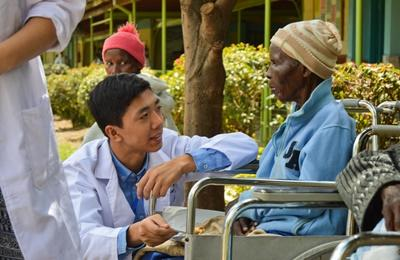 A Projects Abroad Nursing volunteer talks to a patient at a hospital overseas in Nanyuki, Kenya