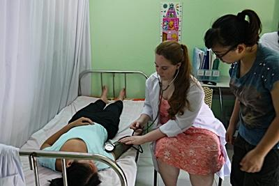 Medical volunteer Kendall Small (USA) learns to take vital signs on fellow Delaware volunteer Selina Su (USA) at Thuy An Rehabilitation Center