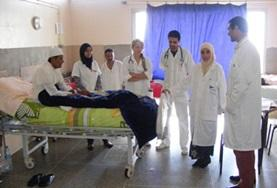 Nursing volunteers doing internships in Morocco observe as a local doctor speaks to a patient about his symptoms.