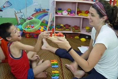 Occupational Therapy volunteer Jillian Meyers (USA) working with physically disabled child at Thuy An Rehabilitation Center