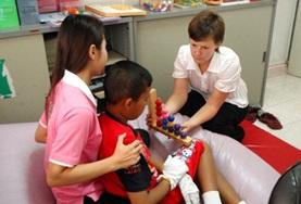 A trained occupational therapist shows a medical intern how to treat a disabled patient at our volunteer placement in Cambodia.