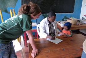 A local occupational therapist demonstrates an assessment technique to a medical intern in Tanzania.