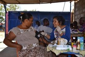 A Pharmacy intern volunteering at an outreach in Ghana helps with distributing medicine to local patients.